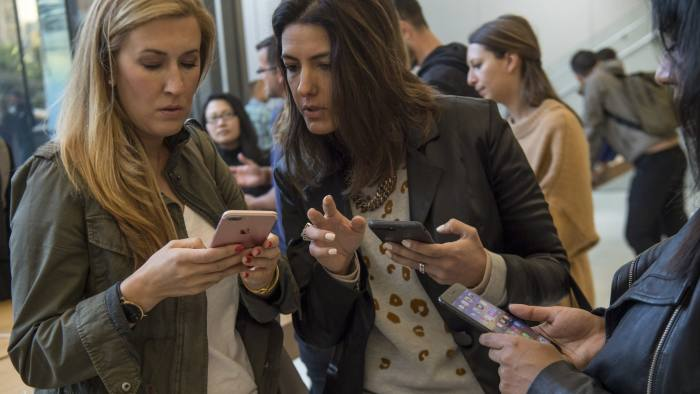 Customers view Apple Inc. iPhone 8 smartphones during the sales launch of the Apple Inc. iPhone 8 smartphone, Apple watch series 3 device, and Apple TV 4K inside a store in San Francisco, California, U.S., on Friday, Sept. 22, 2017. Apple Inc.unveiled its most important new iPhone for years to take on growing competition from Samsung Electronics Co., Google and a host of Chinese smartphone makers. Photographer: David Paul Morris/Bloomberg