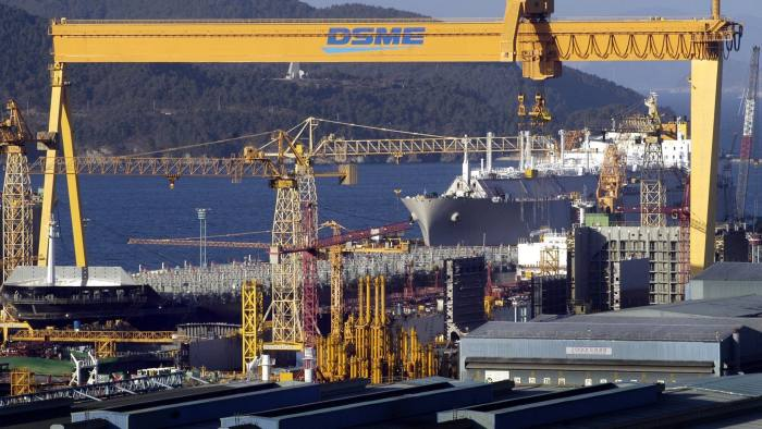 Container ships and tankers are built under a massive construction crane at the Daewoo Shipbuilding & Marine Engineering Co. Ltd. shipyards on Geoje Island in South Korea Monday, November 4, 2003. Photographer: Seokyong Lee/Bloomberg News