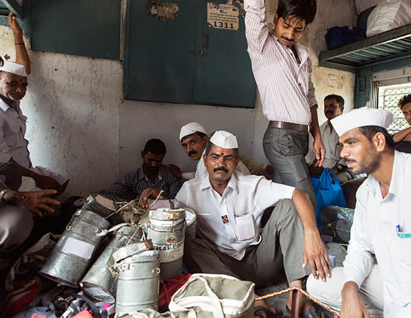 Kedari and fellow dabbawalas take a few moments' rest in the luggage compartment of a train