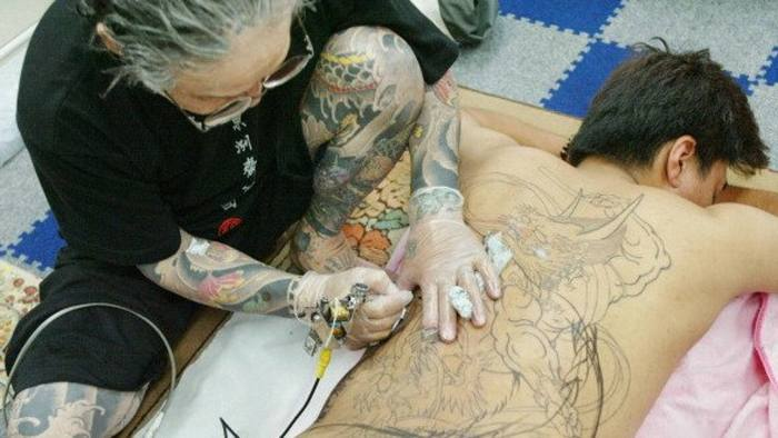 """Japanese tattoo artist Horiyoshi III tattoos a traditional design on the back of a customer at his studio in Yokohama, suburban Tokyo, 06 August 2004. Horiyoshi III, considered one of Japan's greatest living tattooists, gives a whole new meaning to the phrase """"colourful character""""   AFP PHOTO/Toru Yamanaka (Photo credit should read TORU YAMANAKA/AFP/Getty Images)"""