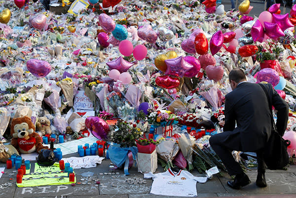 A man crouches in front of flowers, messages and tokens left in tribute to the victims of the attact on Manchester Arena, in central Manchester, Britain May 26, 2017. REUTERS/Stefan Wermuth TPX IMAGES OF THE DAY