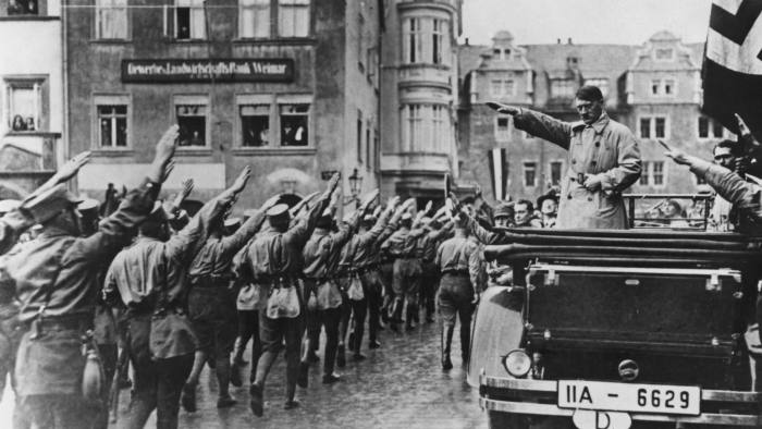Nazi leader Adolf Hitler (1889 - 1945, in car, right) takes the salute as Sturmabteilung (SA) paramilitaries march past in the market square in Weimar, Germany, 13th November 1930. On the far right is Hitler's personal adjutant, Rudolf Hess (1894 - 1987). (Photo by Hulton Archive/Getty Images)