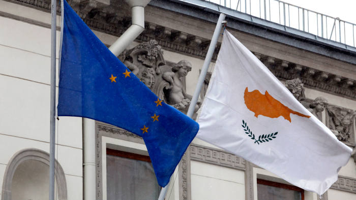 A Cypriot national flag flies alongside a European Union flag outside the Cypriot embassy building in Moscow, Russia