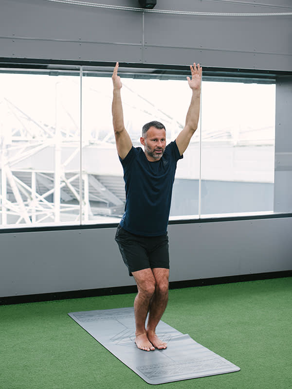Ryan Giggs goes through his yoga exercises against a backdrop of the Old Trafford stadium he graced for many years with Manchester United