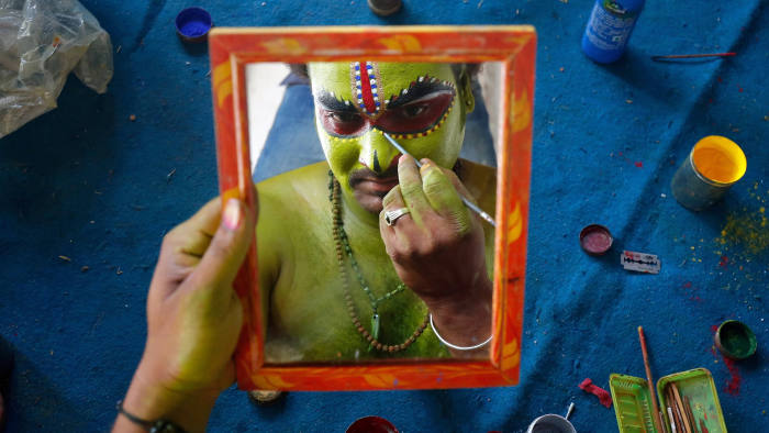 An artiste is reflected in a mirror as he applies make-up backstage before taking part in a celebration to mark Hindu festival of Ramnavami inside the premises of a temple in Bengaluru, India April 5, 2017. REUTERS/Abhishek N. Chinnappa TPX IMAGES OF THE DAY