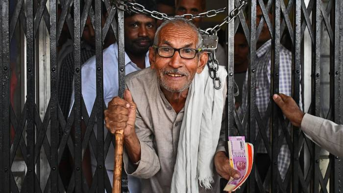 Farmer Vidya Ram exits a bank holding a new Indian two thousand rupee banknote in Dadri, Uttar Pradesh, India, on Tuesday, Nov. 15, 2016. Over a week since Prime Minister Narendra Modi shocked the nation with the withdrawal of large denomination notes there was no sign the government had managed to print enough notes to replace its withdrawal of 86 per cent of currency in circulation. Photographer: Anindito Mukherjee/Bloomberg