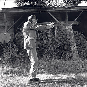 William Burroughs firing his pistol with his marijuana crop in the background in Kansas, 1991