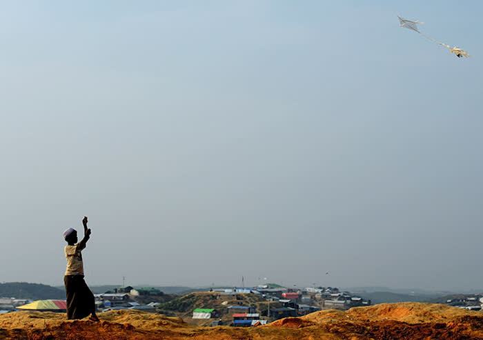 TOPSHOT - A Rohingya refugee boy flies a kite at Balukhali refugee camp in the Bangladeshi district of Ukhia on November 22, 2017. An estimated 618,000 Muslim Rohingya have fled mainly Buddhist Myanmar since a military crackdown was launched in Rakhine in August triggered an exodus, straining resources in the impoverished country. / AFP PHOTO / Munir UZ ZAMANMUNIR UZ ZAMAN/AFP/Getty Images
