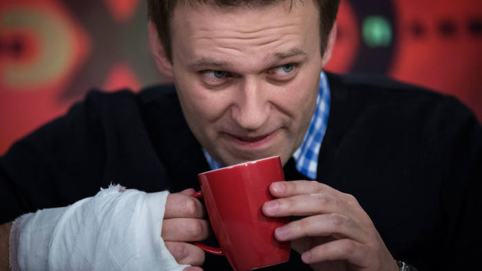Russian opposition leader Alexey Navalny drinks tea while speaking to a journalist during an interview