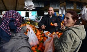 PARIS, FRANCE - NOVEMBER 18: A woman buys fruit at the Marche Barbes, the outdoor market located in the 18th arrondissement of Paris as normal life resumes in the area on November 18, 2015 in Paris, France. Barbes is a neighbourhood in Paris with a large amount of Muslim residents. Following the terrorist attacks in Paris on Friday which claimed 129 lives and injured many more, the Muslim community of Paris has seen an increase in security checks, adding to tension in the community. (Photo by Frederic T Stevens/Getty Images)