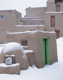 Adobe houses covered in snow in Taos Pueblo