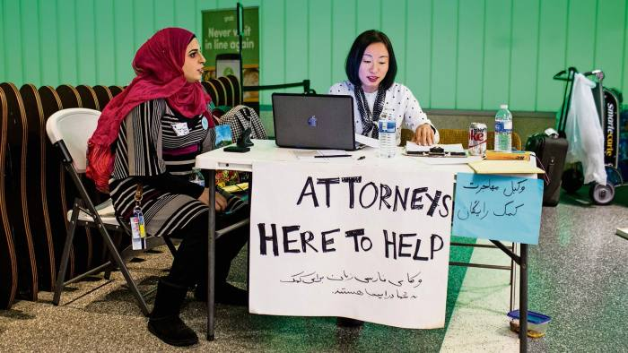 Volunteer translator Nour Our (L) and volunteer attorney Kat Choi (R) sit in the arrivals area during a protest of the executive order by US President Donald Trump, banning immigrants from seven majority-Muslim countries at Los Angeles International Airport in Los Angeles, California, February 4, 2017. / AFP / Kyle Grillot (Photo credit should read KYLE GRILLOT/AFP/Getty Images)