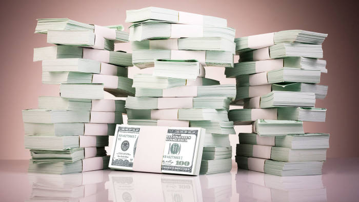 Pile of money stacked on reflective surface