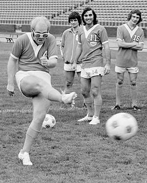 Elton John, co-owner of the LA Aztecs in the 1970s, takes a kick in front of star player George Best