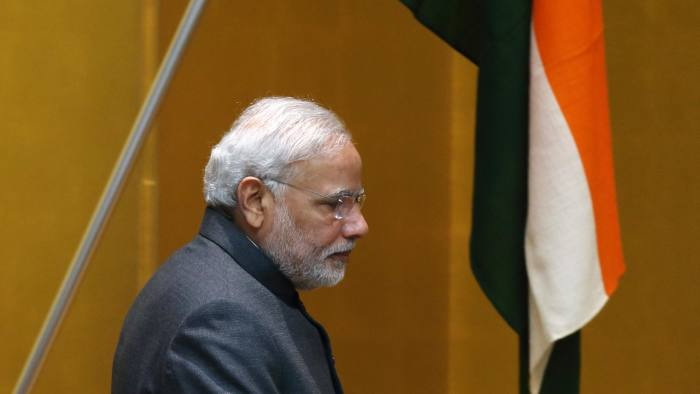 Narendra Modi, India's prime minister, walks past India's national flag as he leaves the podium after making a speech during a luncheon with Japanese business groups at the headquarters of the business lobby Keidanren in Tokyo, Japan, on Monday, Sept. 1, 2014. Modi is in Japan to boost ties between Asia's second- and third-biggest economies, both of which are embroiled in territorial disputes with an increasingly assertive China. Photographer: Tomohiro Ohsumi/Bloomberg *** Local Caption *** Narendra Modi