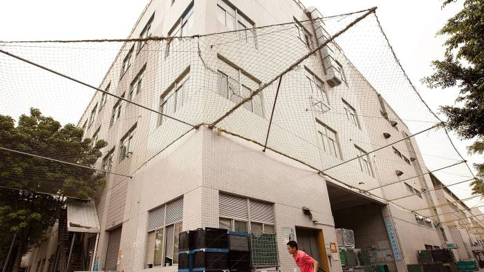 A man walks past a building surrounded by safety netting at the Longhua Science & Technology Park, also known as Foxconn city, in Shenzhen, China, on Monday, April 18, 2011. As warmer ties with former civil-war foe China encourage an exodus of factories to the lower-cost mainland, Taiwan's failure to develop new growth industries has caused it to fall behind Singapore and Hong Kong. Photographer: Forbes Conrad/Bloomberg