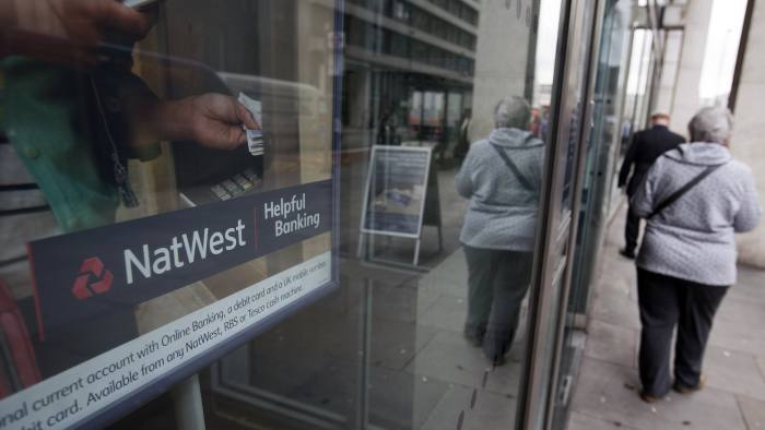 Pedestrians pass a branch of a NatWest bank, part of the Royal Bank of Scotland Group Plc (RBS), in London, U.K., on Tuesday, April 16, 2013. The U.K.'s consumer-finance regulator is probing technology failures at Royal Bank of Scotland Group Plc, which left some customers at the lender's NatWest and Ulster Bank units unable to withdraw money. Photographer: Simon Dawson/Bloomberg