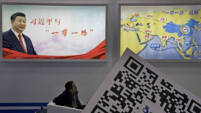 In this April 28, 2017 photo, an attendee at a conference looks up near a portrait of Chinese President Xi Jinping with the words