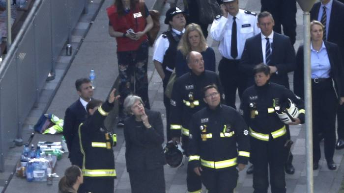 British Prime Minister Theresa May (C) speaks with Dany Cotton (L), London Fire Brigade commissioner as she visits the remains of Grenfell Tower, a residential tower block in west London which was gutted by fire on June 15, 2017. Firefighters searched for bodies today in a London tower block gutted by a blaze that has already left 12 dead, as questions grew over whether a recent refurbishment contributed to the fire. / AFP PHOTO / Tolga AKMEN (Photo credit should read TOLGA AKMEN/AFP/Getty Images)