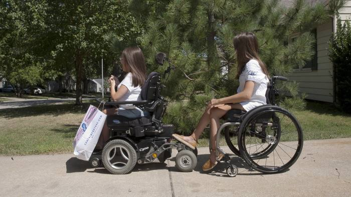 Lauren Gibbs, right, follows her sister's electronic wheelchair outside their home in Roeland Park, Kansas, U.S., on Thursday, Aug. 11, 2016. Gibbs, who was born with spinal muscular atrophy, enrolled in a trial of an experimental drug, called nusinersen, developed by a startup, Ionis Pharmaceuticals Inc., and biotech giant Biogen Inc. Photographer: Uno Yi/Bloomberg