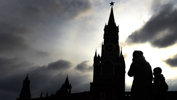 People walk across Red Square, with the Kremlin's Spasskaya (Saviour) Tower seen in the background, in central Moscow on October 9, 2016. / AFP / VASILY MAXIMOV (Photo credit should read VASILY MAXIMOV/AFP/Getty Images)