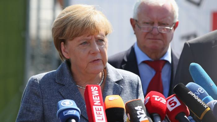 HEIDENAU, GERMANY - AUGUST 26: German Chancellor Angela Merkel speaks to the media after spending over an hour visiting the aslyum shelter that was the focus of recent violent protests on August 26, 2015 in Heidenau, Germany. Onlookers booed as she arrived and right-wing demonstrators clashed violently with police last weekend near the shelter. This is Merkel's first visit to a shelter for migrants seeking asylum in Germany. Germany is expecting to receive at least 800,000 migrants and refugees this year and is struggling to house them and process their asylum applications. (Photo by Sean Gallup/Getty Images)