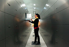 A woman takes a deposit box out of a compartment in the safe room of an Austrian bank in Vienna April 10, 2013