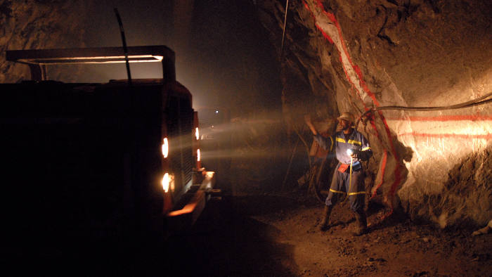 A miner directs a truck carrying ore at Metorox's Chibuluma copper mine, near Kitwe, Zambia, on Thursday Feb. 7, 2008. The price of copper, Zambia's largest export, has surged more than threefold this decade. Photographer: Naashon Zalk/Bloomberg News