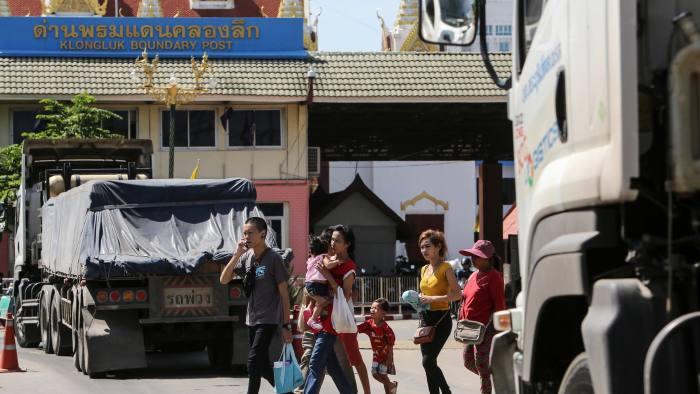 Pedestrians cross a road between trucks waiting to cross the border into Cambodia in Aranyaprathet, Thailand