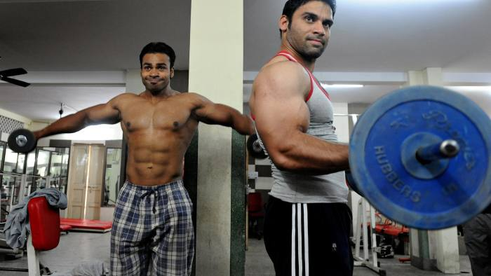 To go with Lifestyle-India-health-Bollywood,FEATURE by Rupam Jain Nair Indian bodybuilders Rahul Kumar (L) and Tanveer Akram (R) work out in a gymnasium in New Delhi on October 13, 2009. For bodybuilder Raghu Ghai, days begin and end at the same place--the gym, where he pursues the quest for glistening slab-like pecs, six-pack abs and bulging biceps, all new indicators of Indian male physique. 28-year-old Ghai says his body obsession was triggered by Bollywood's leading actors who suddenly started hitting the gym, adding brawn and biceps to send a clear signal: masculinity has turned a corner in a country where male grooming was until recently an irrelevant subject. AFP PHOTO/Prakash SINGH (Photo credit should read PRAKASH SINGH/AFP/Getty Images)