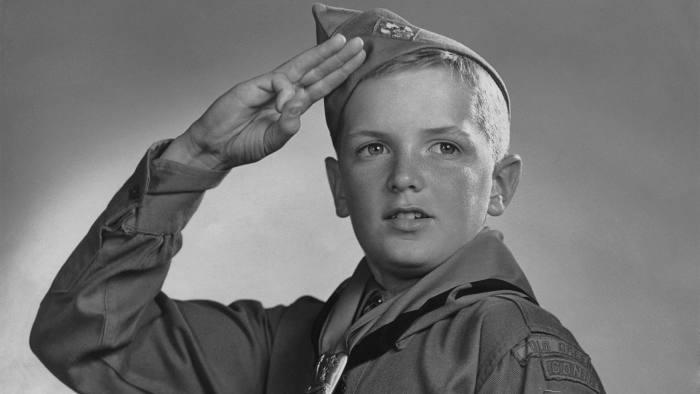 A saluting boy scout in uniform circa 1950