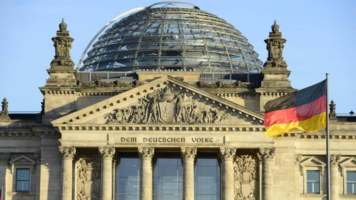 """The German national flag is seen in front of the Reichstag building housing the German parliament Bundestag on December 16, 2013 on the eve of the swearing-in ceremony of the German chancellor and the new cabinet. Merkel, whose conservative party CDU triumphed in the September 22, 2013 general election but fell short of an absolute majority, is to be sworn in for a third term, launching a """"grand coalition"""" government with her traditional rivals the Social Democrats (SPD). AFP PHOTO / JOHN MACDOUGALL (Photo credit should read JOHN MACDOUGALL/AFP/Getty Images)"""