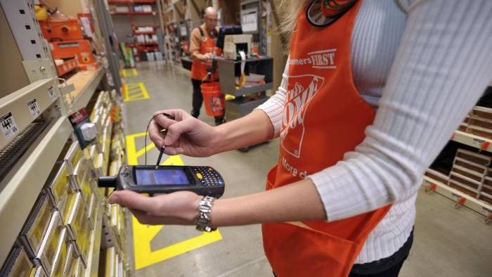 Brandi Bishop, a specialty assistant manager for Home Depot, checks inventory with a new portable device while fellow employee W.T.