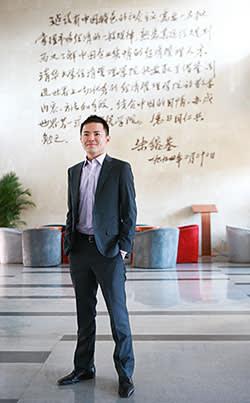 Mr. Masahiro Okumura poses in front of an inscription of former Chinese Premier Zhu Rongji at Tsinghua University