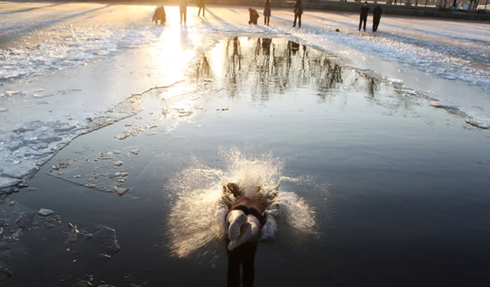 A winter swimmer dives into the icy waters of a river at a park in Shenyang, Liaoning province, China December 18, 2017. REUTERS/Stringer ATTENTION EDITORS - THIS IMAGE WAS PROVIDED BY A THIRD PARTY. CHINA OUT.