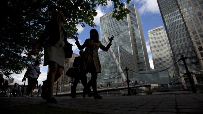 Pedestrians walk along the dockside near the offices of JPMorgan Chase & Co., center, in the Canary Wharf business district in London, U.K., on Monday, Aug. 12, 2013. The U.S. may announce charges as early as this week against former London-based JPMorgan employees related to allegations they tried to conceal losses last year, a person familiar with the matter said. Photographer: Simon Dawson/Bloomberg