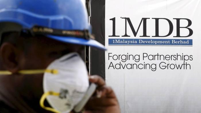 A construction worker talks on the phone in front of a 1Malaysia Development Berhad (1MDB) billboard at the Tun Razak Exchange development in Kuala Lumpur, Malaysia, February 3, 2016. Picture taken February 3, 2016. REUTERS/Olivia Harris/Files