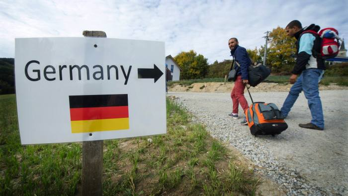 epa04966105 Refugees from Syria walk past a sign that reads 'Germany' and features an image of the German national flag near the Austrian-German border in Julbach, Austria, 06 October 2015. Austria has become the main transit country for migrants travelling from the Balkans to Germany while Italy had faced the brunt of refugee arrivals via the Mediterranean Sea. EPA/ARMINWEIGEL
