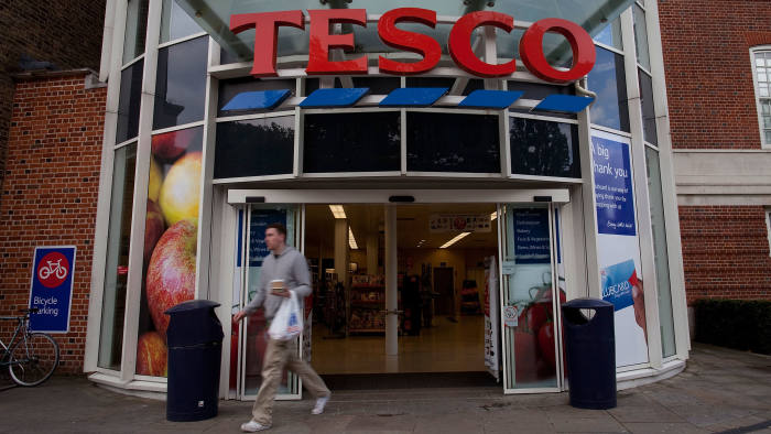 A customer exits a Tesco Plc store in London, UK
