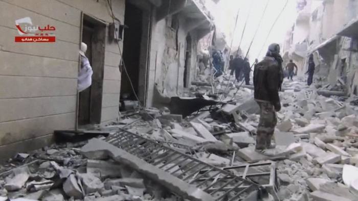 In this image taken from video obtained from the Aleppo News Network, which has been authenticated based on its contents and other AP reporting, people walk on a street covered with the rubble of damaged buildings after activists said a barrel bomb was dropped in Aleppo, Syria, Thursday, Feb. 6, 2014. Syrian rebels launched a new push in the northern province of Aleppo on Thursday to capture key symbols of the government and stormed a major section of a prison there, freeing hundreds of prisoners in the process, activists said. The advance came amid a relentless air campaign by government forces in Aleppo. (AP Photo/Aleppo News Network)