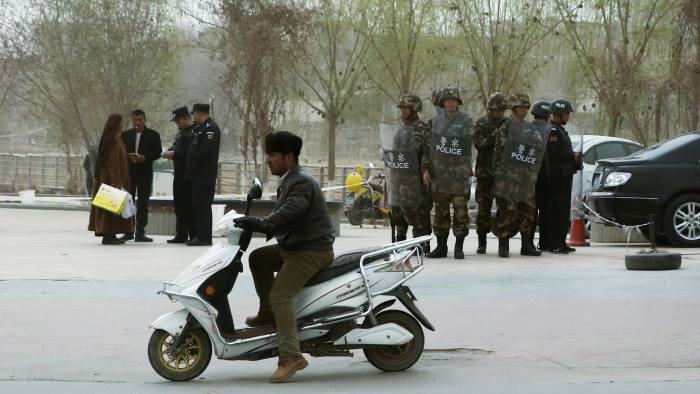 Police officers check the identity cards of a people as security forces keep watch in a street in Kashgar, Xinjiang Uighur Autonomous Region, China, March 24, 2017. REUTERS/Thomas Peter - RC1A412EF700