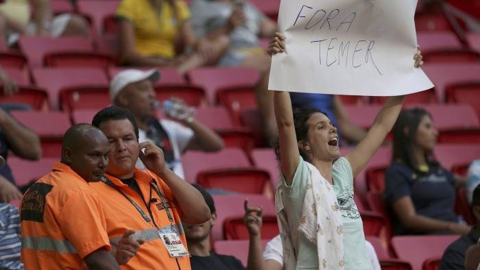 2016 Rio Olympics - Soccer - Preliminary - Women's First Round - Group F Germany v Canada - Mane Garrincha Stadium - Brasilia, Brazil - 09/08/2016.  Security looks on as a demonstrator holds up a placard in protest of interim President of Brazil Michel Temer in grandstand during soccer match between Canada and Germany.  REUTERS/Ueslei Marcelino  FOR EDITORIAL USE ONLY. NOT FOR SALE FOR MARKETING OR ADVERTISING CAMPAIGNS.