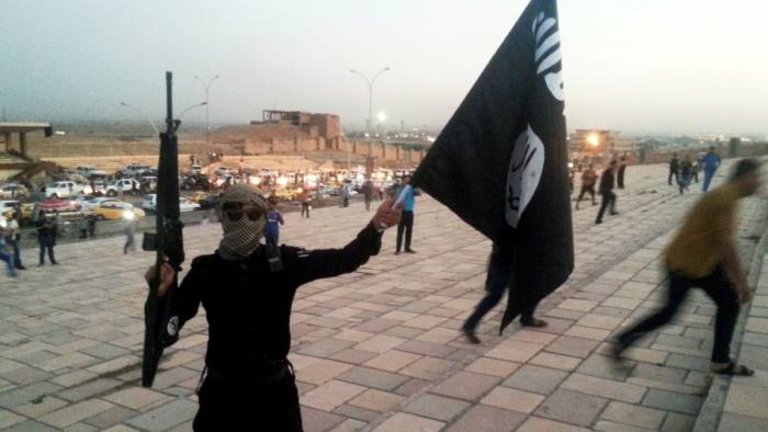 FILE PHOTO: A fighter of the Islamic State of Iraq and the Levant (ISIL) holds an ISIL flag and a weapon on a street in the city of Mosul June 23, 2014. REUTERS/Stringer/File Photo