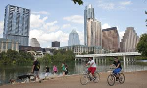 Cyclists pass beneath the downtown skyline on the hike and bike trail on Lady Bird Lake in Austin, Texas September 18, 2012. The 10.1 mile trail runs along the Colorado river through downtown. In Austin, flip-flop-wearing University of Texas students mingle with coat-tie-and-boot-clad state lawmakers and technology workers in jeans. The Lone Star State capital prides itself on its slacker vibe, but it's also the place where a college student named Michael Dell once started a computer business and where Whole Foods Market started and has its headquarters. Picture taken September 18, 2012. REUTERS/Julia Robinson (UNITED STATES - Tags: CITYSPACE SOCIETY TRAVEL) - RTR38JZI