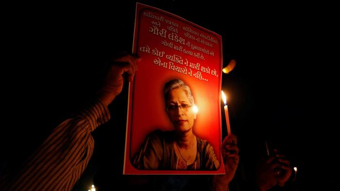 People hold placards and candles during a vigil for Gauri Lankesh, a senior Indian journalist who according to police was shot dead outside her home on Tuesday by unidentified assailants in southern city of Bengaluru, in Ahmedabad, India, September 6, 2017. REUTERS/Amit Dave - RC1D524C5ED0
