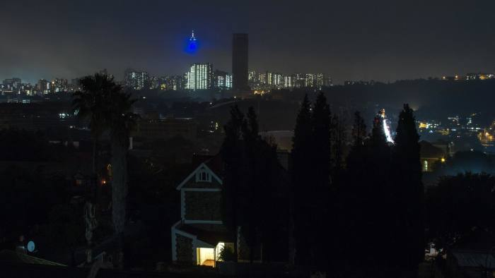 The Ponte tower, center, stands without electrical power as darkness surrounds residential homes due to a load shedding blackout by Eskom Holdings SOC Ltd. in the Troyeville suburb of Johannesburg, South Africa, on Monday, Nov. 3, 2014. Eskom said South Africa's power supply remains strained as it investigates what caused a silo storing coal to collapse, forcing the state-owned utility to cut electricity to customers. Photographer: Dean Hutton/Bloomberg