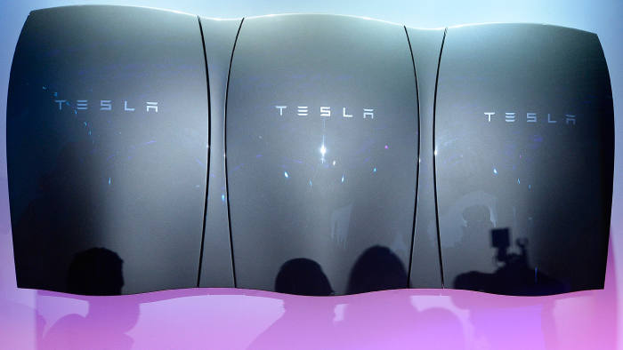 Guests pose with the Powerwall unit after Elon Musk, CEO of Tesla unveiled suit of batteries for homes, businesses, and utilities at Tesla Design Studio April 30, 2015 in Hawthorne, California