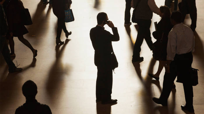 A man stands in the middle of Grand Central Terminal as he speaks on a cell phone