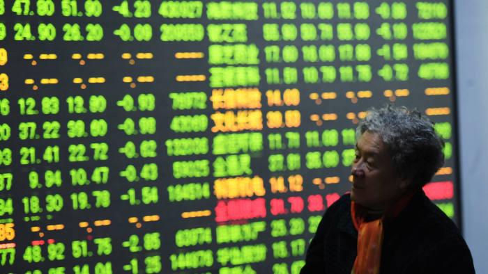 A woman walks past a screen in the brokerage house in Hangzhou, Zhejiang province, China
