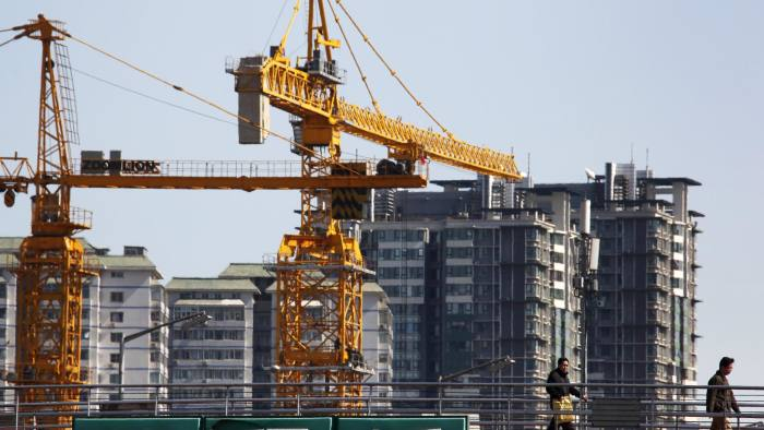 Pedestrians walk past cranes and residential buildings standing under construction in Beijing, China, on Tuesday, March 10, 2015. China set the lowest economic growth target in more than 15 years and flagged increasing headwinds that include a property slump, excess industrial capacity and disinflation. Photographer: Tomohiro Ohsumi/Bloomberg